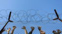 Immigrants lean on the fences during an unrest inside Pagani detention centre, in the eastern Aegean island of Lesvos